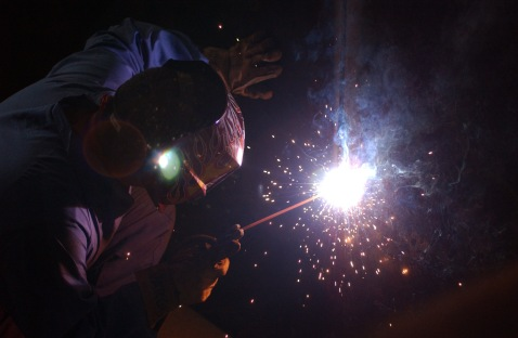 Welder constructs some gun boxes for Iraqi trucks.
